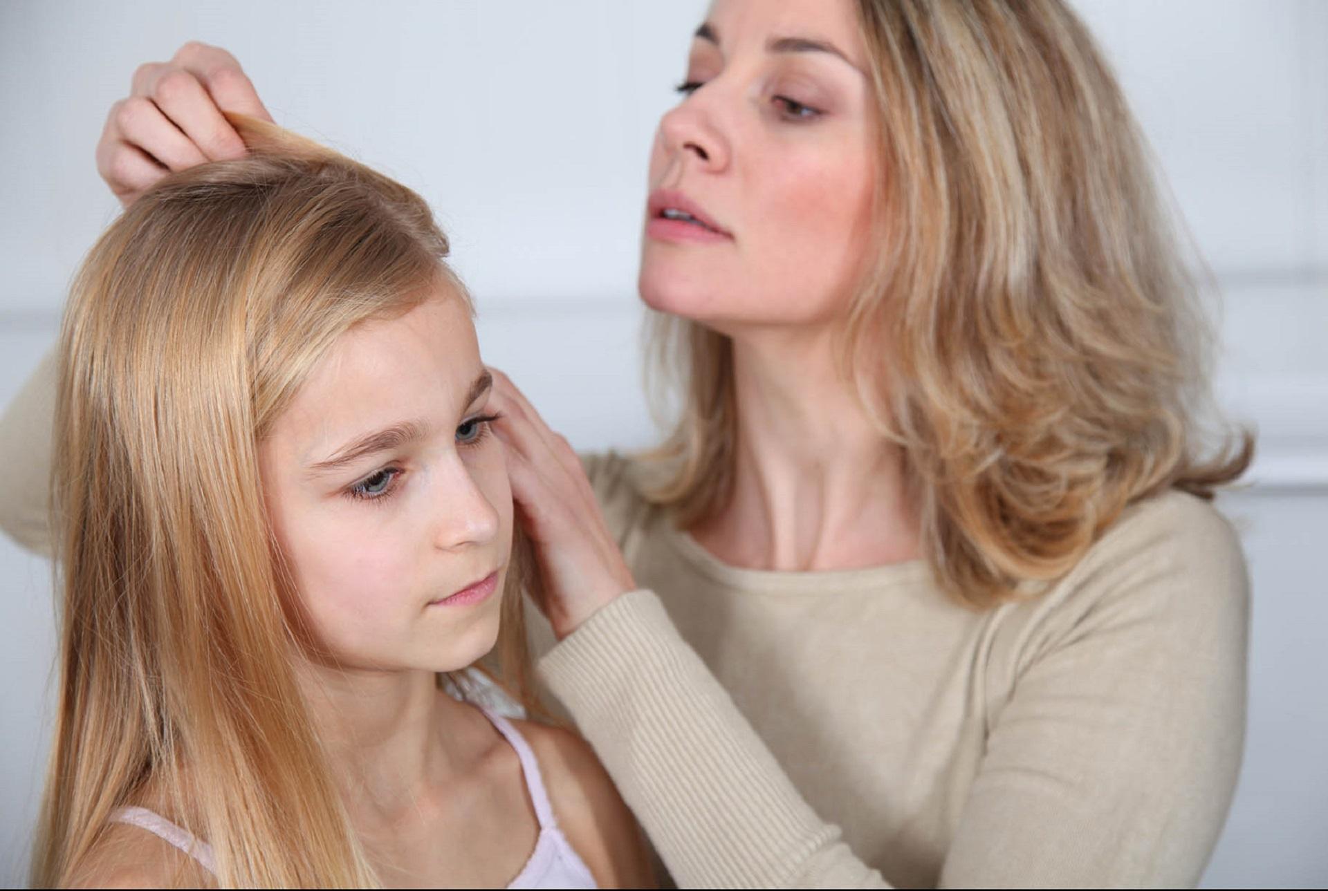 mamma controlla i capelli della figlia per vedere se ha i pidocchi