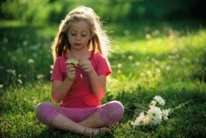 bambina seduta su un prato in mezzo alla natura
